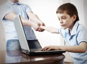 Father dragging son from the computer. Parent pulling child from laptop. Computer Addiction